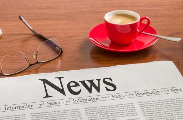 A newspaper on a wooden desk - News