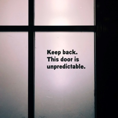 glass panel door with sign that says Keep Back. This door is unpredictable.