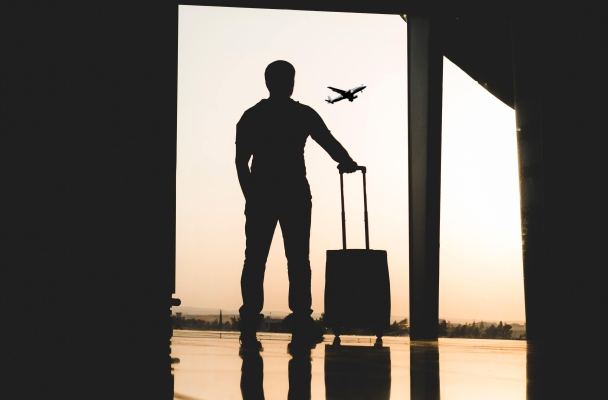 person at airport watching plane take off